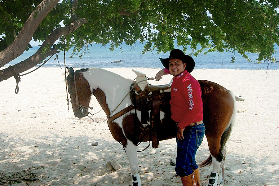 Mexican ranchero with his horse on the beach